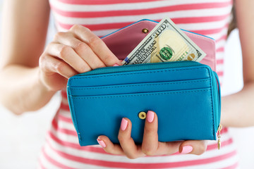 Young woman getting dollar banknote from purse