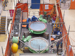 Engineers repairing flange valves during power station outage, high angle  view
