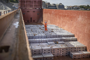 Worker standing on metal ingots in ship's hold