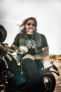 Portrait of mature man sitting on motorcycle on arid plain, Cagliari, Sardinia, Italy