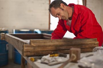 Carpenter working on wooden frame