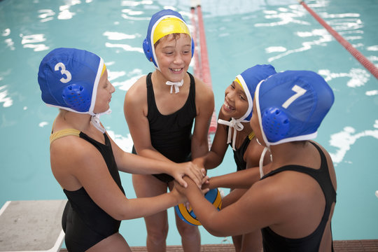 Four schoolgirl water polo players holding hands poolside