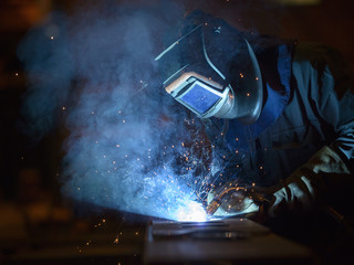 Welder using oxyacetylene torch in factory