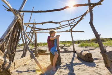 Boy making a break in driftwood shelter, Caleri Beach, Veneto, Italy