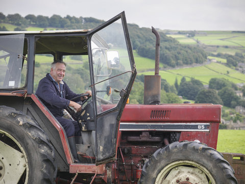 Mature farmer smiling in tractor