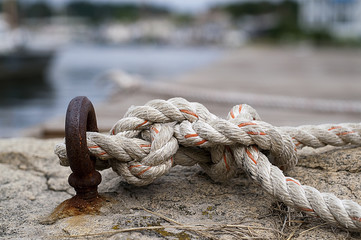 Rope tied with nautical knot, with blurry harbor visible in the background