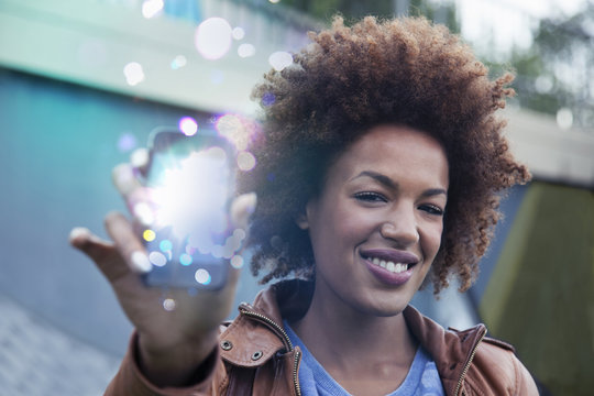 Young woman holding up smartphone with glowing lights coming out