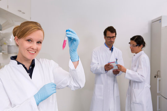 Group of scientists at work in laboratory, Cell culture suspension (front), which is later used for western blot technique (back) to see which proteins are pathologically expressed
