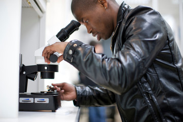 Young man looking through microscope doing metalwork