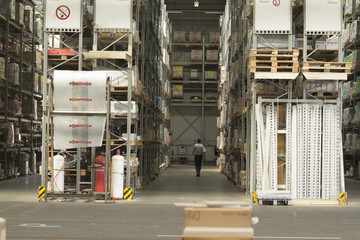 Worker searching for stock in aisles of hardware store warehouse