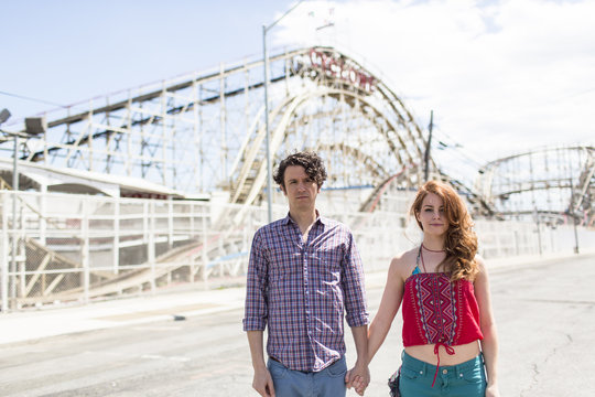 Portrait of couple with blank expressions at amusement park