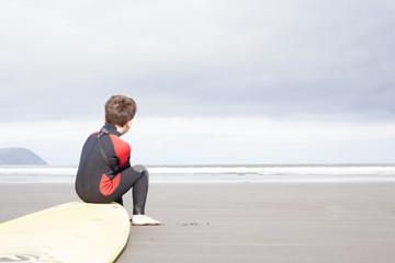 Boy sitting on surfboard on beach