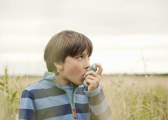 Anxious boy using inhaler outdoors