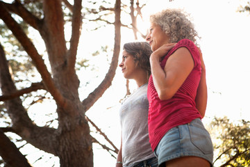Mother and daughter looking into distance, tree in background