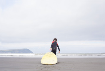 Boy pulling surfboard on beach
