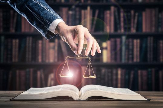 重厚な本と金色の天秤