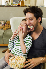 Father and young son with mouthfuls of popcorn