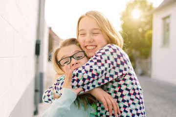 Two sisters hugging enthusiastically
