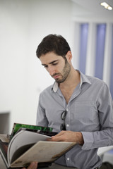 Male office worker reading book