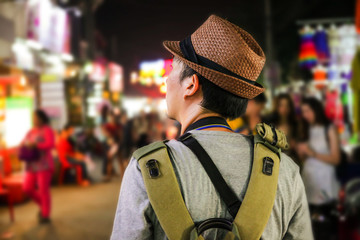 Young male backpacker walking in a famous street night market in Siem Reap, Cambodia