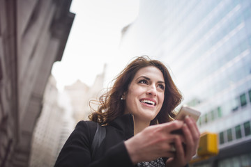 Young woman holding cellphone, New York, USA