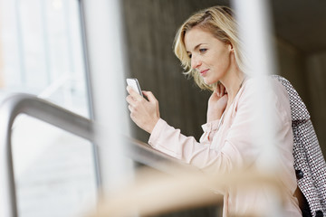 Businesswoman using mobile phone in office building