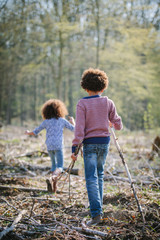 Brother and sister walking together in woods