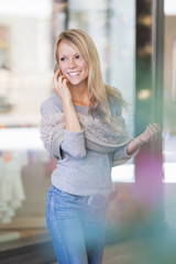 Smiling young woman chatting on smartphone in front of shop window