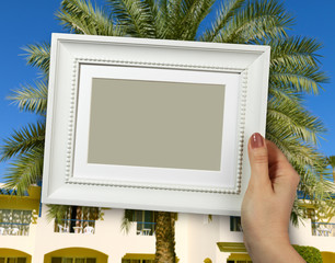 Wooden frame in woman hands. background of the Egyptian hotel