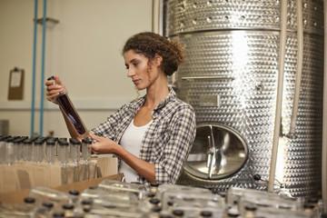 Woman looking at bottle in distillery