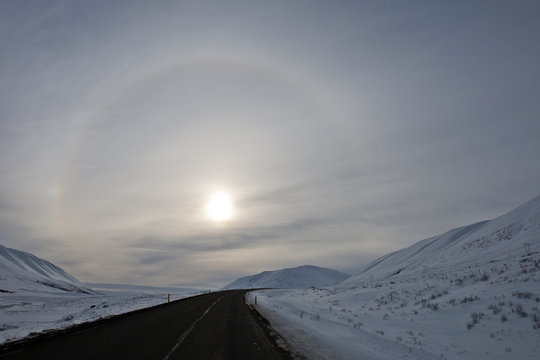 Sun with halo in pale winter landscape, Godafoss, North Iceland