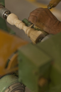 Close up of carpenter turning wood with chisel in workshop