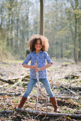 Portrait of young girl in woods holding a stick