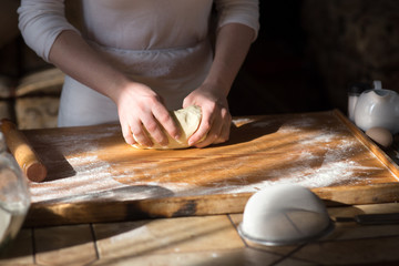 Baker hands kneading dough in flour 