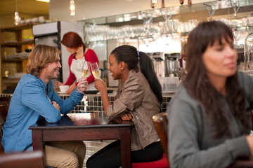Young couple in cafe bar toasting with white wine