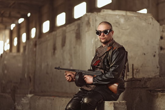 Portrait of a man from post-apocalyptic world with machine gun and the black glasses in an abandoned building