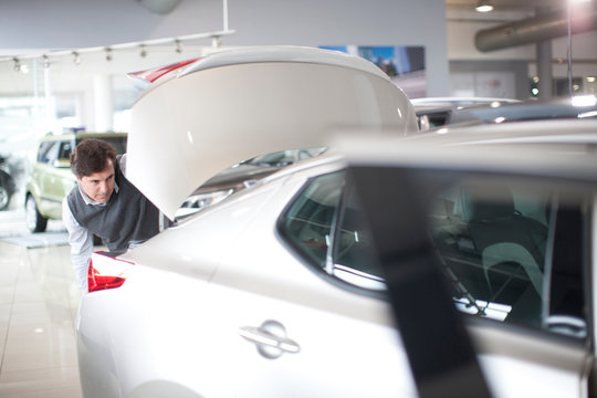 Mid adult man checking car boot in car showroom