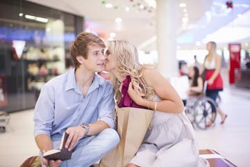 Young woman kissing man's cheek at mall