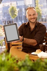 Happy man holding tablet with blank screen