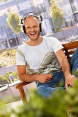 Happy man enjoying music outdoors