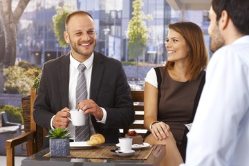 Businessmen and businesswoman relaxing at cafe