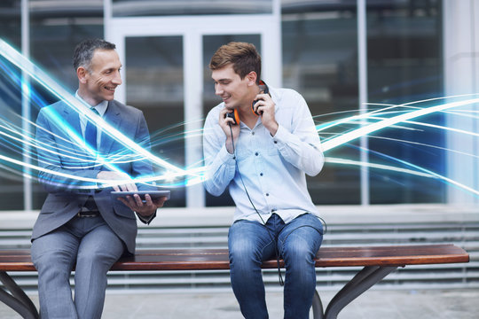 Businessman and young man watching digital tablet and waves of blue light