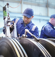 Engineers fitting blades to steam turbine in repair works