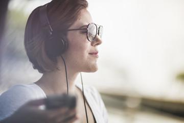 Mid adult woman listening to music on headphones