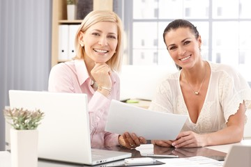 Happy casual businesswomen working at office desk