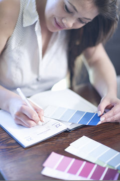 Interior designer with swatches writing in diary