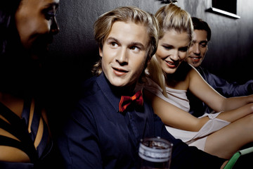 Young men and women sitting together in nightclub