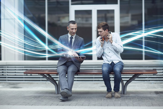 Businessman and young man watching digital tablet and waves of illumination