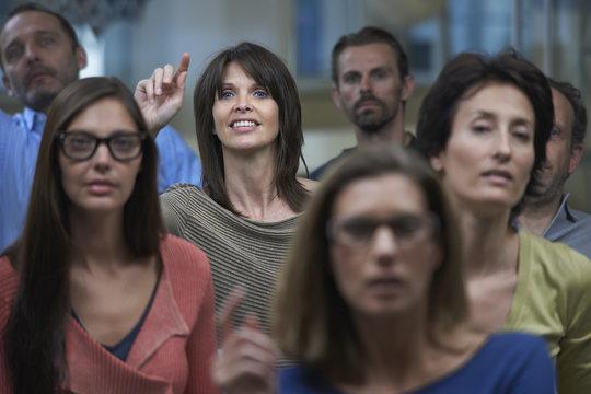 Group watching presentation, woman raising hand