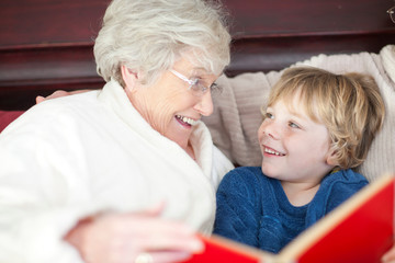 Grandmother and grandson reading in bed